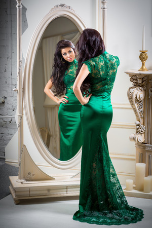woman mirror: Beautiful sexy young woman in green evening dress is looking at the mirror Stock Photo