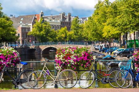 Jízdní kola na mostě přes kanály v Amsterdamu. Amsterdam je hlavní a nejlidnatější město Nizozemska Reklamní fotografie - 38333804