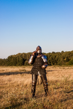 crusade: Medieval knight in the field with an axe Stock Photo