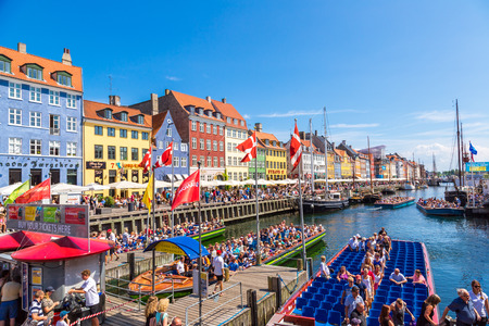 COPENHAGEN, DENMARK - JULY 25: Nyhavn district is one of the most famous landmark in Copenhagen. People enjoy sunny weather in open cafees in Copenhagen on July 25, 2014