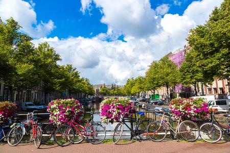 bicicleta: Bicicletas en un puente sobre los canales de Amsterdam. Amsterdam es la capital y ciudad más poblada de los Países Bajos