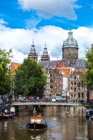 populous: Canal and St. Nicolas Church in Amsterdam. Amsterdam is the capital and most populous city of the Netherlands Stock Photo