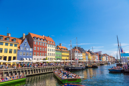 Nyhavn district is one of the most famous place in Copenhagen, Denmark in a summer day