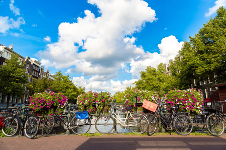 amsterdam: Bicycles on a bridge over the canals of Amsterdam. Amsterdam is the capital and most populous city of the Netherlands