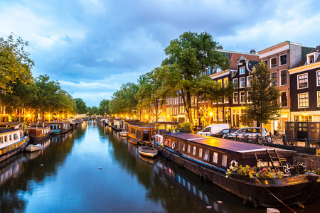 amstel river: Canals of Amsterdam at night. Amsterdam is the capital and most populous city of the Netherlands Stock Photo