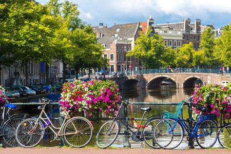 Jízdní kola na mostě přes kanály v Amsterdamu. Amsterdam je hlavní a nejlidnatější město Nizozemska Reklamní fotografie