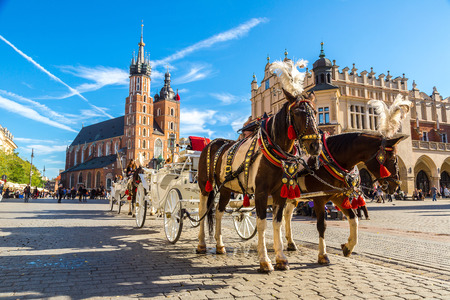 church: Horse carriages at main square in Krakow in a summer day, Poland