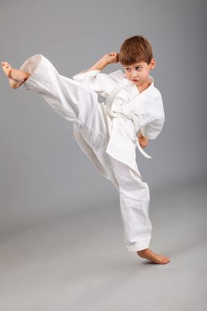 patada: Muchacho del karate en el kimono blanco combates aislados sobre fondo gris