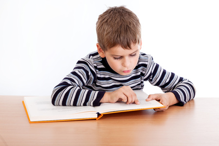 Cute schoolboy is reading a book isolated on a white background photo