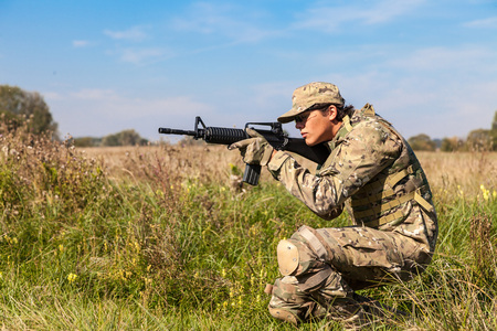 Soldier with a rifle in the field photo