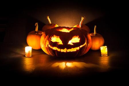 calabaza: Calabaza de Halloween con velas sobre un fondo negro