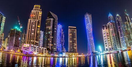 marina: Dubai downtown night scene with city lights, luxury new high tech town in middle East. Dubai Marina cityscape, UAE.