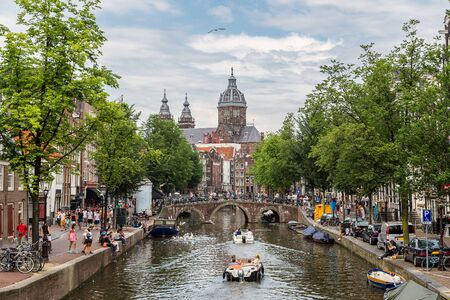 amsterdam: Canal and St. Nicolas Church in Amsterdam, Netherlands in a summer day Editorial