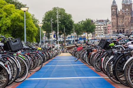 bicicleta: Aparcamiento de bicicletas enorme en el centro de Amsterdam, en un día de verano Foto de archivo