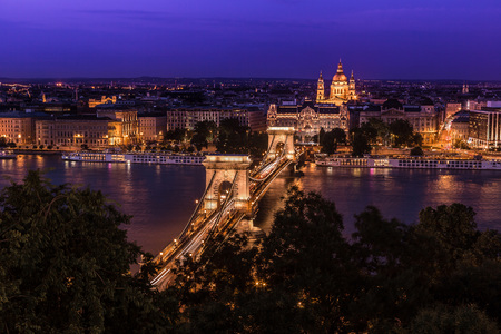 building a chain: River view of Budapest at evening, illuminated Chain Bridge and Parliament Building.