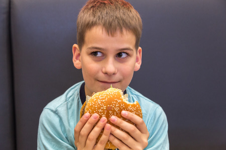 Cute caucasian boy is eating big burger photo