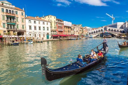 VENICE, ITALY - JUNE 18, 2014: Gondola at the Rialto bridge in Venice, in a beautiful summer day in Italy on June 18