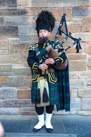 bagpipes: EDINBURGH, SCOTLAND - JUNE 25, 2016: Bagpiper playing music with bagpipe in Edinburgh Castle, Scotland, United Kingdom on June 25, 2016 Editorial