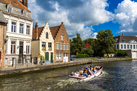 14: BRUGES, BELGIUM - JUNE 14, 2016: Tourist boat on canal in Bruges in a beautiful summer day, Belgium on June 14, 2016 Editorial