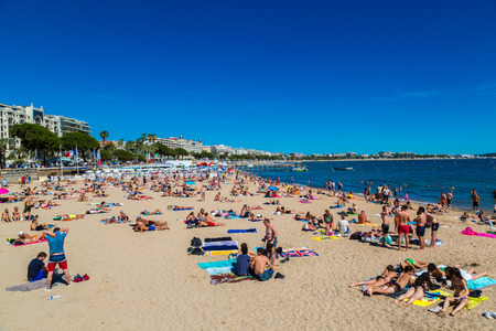 CANNES, FRANCE - JUNE 23, 2016: People on popular beach in Cannes in a beautiful summer day, France on June 23, 2016