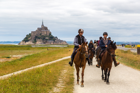 camargue: MONT SAINT MICHELE, FRANCE - JUNE 27, 2016: People riding on horse back at the Mont Saint Michele abbey, France on June 27, 2016