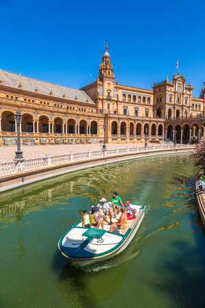 SEVILLA, SPAIN - JUNE 11, 2016: Tourists float on a boat on the canal Spanish Square (Plaza de Espana), Spain on June 11, 2016