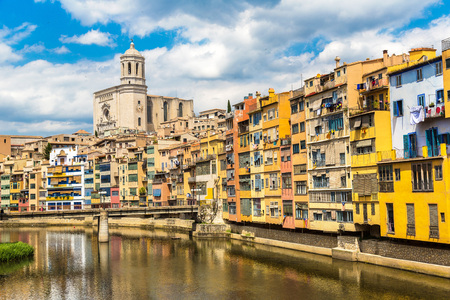 Colorful houses and Saint Mary Cathedral at background in Girona, in a beautiful summer day, Catalonia, Spain