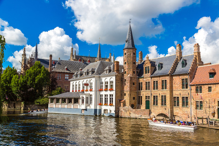 Tourist boat on canal in Bruges in a beautiful summer day, Belgium