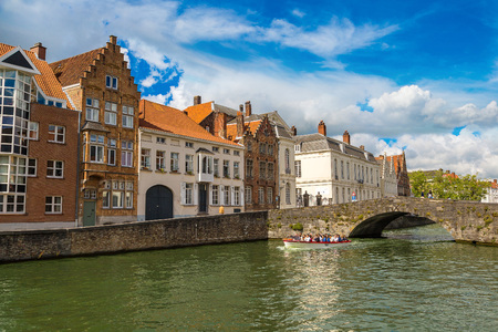 benelux: BRUGES, BELGIUM - JUNE 14, 2016: Tourist boat on canal in Bruges in a beautiful summer day, Belgium on June 14, 2016 Editorial