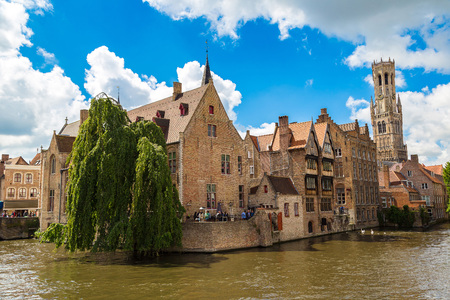 Canal in Bruges and famous Belfry tower on the background in a beautiful summer day, Belgium