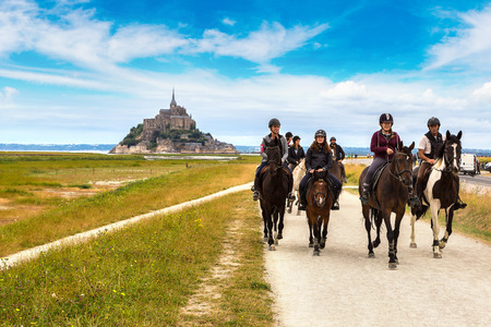 MONT SAINT MICHELE, FRANCE - JUNE 27, 2016: People riding on horse back at the Mont Saint Michele abbey, France on June 27, 2016