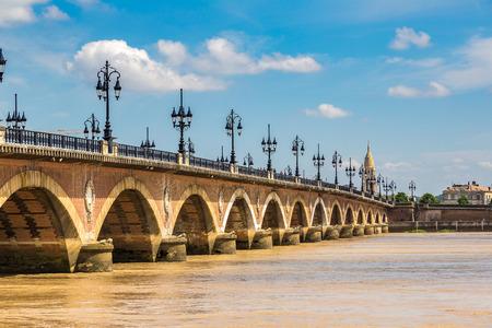 Pont de pierre, old stony bridge in Bordeaux in a beautiful summer day, France