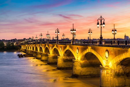 Pont de pierre, old stony bridge in Bordeaux in a beautiful summer night, France
