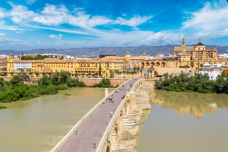 The Great Mosque (Mezquita Cathedral) and Roman Bridge on Guadalquivir river in Cordoba in a beautiful summer day, Spain
