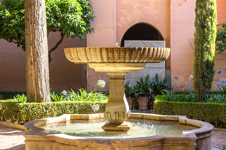 A fountain in the Moorish palace in Alhambra palace in Granada in a beautiful summer day, Spain