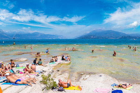 16: SIRMIONE, ITALY - JUNE 16, 2016: Garda lake, Public beach in Sirmione in a beautiful summer day, Italy on June 16, 2016