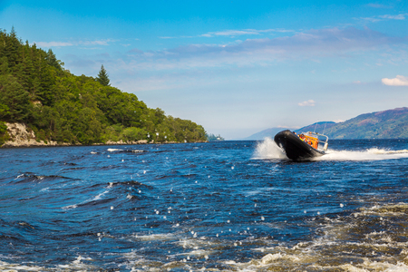 ness river: LOCH NESS, SCOTLAND - JUNE 27, 2016: Speedboat on the Loch Ness lake in Scotland in a beautiful summer day, United Kingdom on June 27, 2016