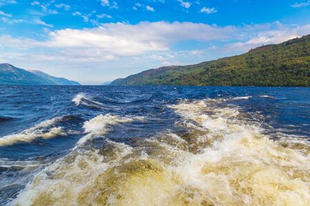 Trail on water surface behind motor boat on Loch Ness in Scotland in a beautiful summer day, United Kingdom Stock Photo