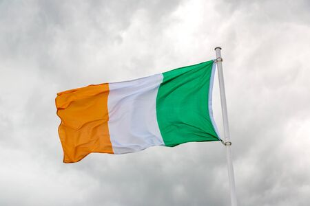 Irish flag waving in the wind against cloudy sky Stock Photo