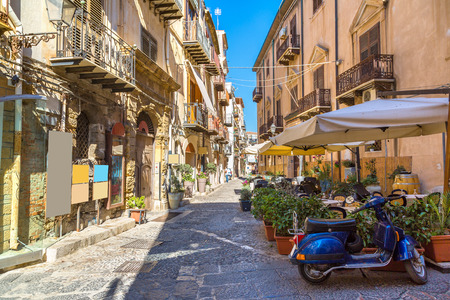 Narrow street in the old town of Cefalu in Sicily, Italy in a beautiful summer day