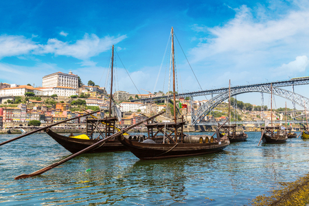 dom: Traditional boats with wine barrels and Douro River in Porto in a beautiful summer day, Portugal
