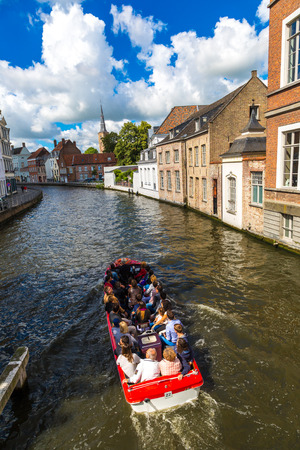 BRUGES, BELGIUM - JUNE 14, 2016: Tourist boat on canal in Bruges in a beautiful summer day, Belgium on June 14, 2016 Editorial