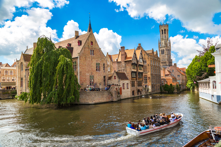 BRUGES, BELGIUM - JUNE 14, 2016: Canal in Bruges and famous Belfry tower on the background in a beautiful summer day, Belgium on June 14, 2016