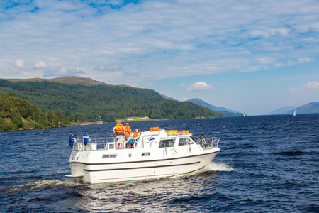 ness river: LOCH NESS, SCOTLAND - JUNE 27, 2016: Boat on the Loch Ness lake in Scotland in a beautiful summer day, United Kingdom on June 27, 2016