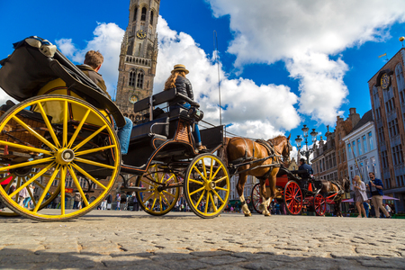 BRUGES, BELGIUM - JUNE 14, 2016: Horse carriage in the Market square in Bruges in a beautiful summer day, Belgium on June 14, 2016 Editorial