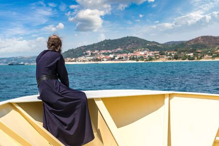 Old monk is looking at mountains Athos on a ship in a summer day