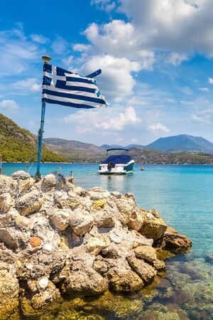 Vouliagmeni lake and greek flag  near Loutraki in a summer day, Greece