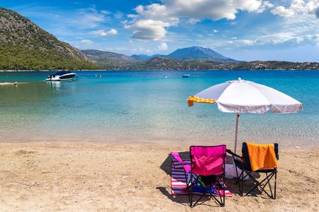 Umbrella and sundecks on sandy beach near Loutraki in a summer day, Greece