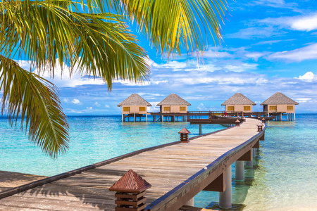 MALDIVES - JUNE 24, 2018: Water Villas (Bungalows) and wooden bridge at Tropical beach in the Maldives at summer day 報道画像