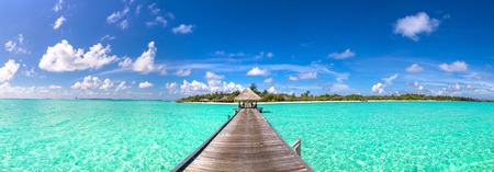 Panorama of Water Villas (Bungalows) and wooden bridge at Tropical beach in the Maldives at summer day